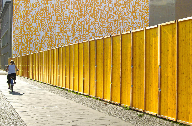 woman riding bicycle along yellow wall